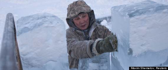 Ruslan, 35, loads blocks of ice onto a truck outside Yakutsk