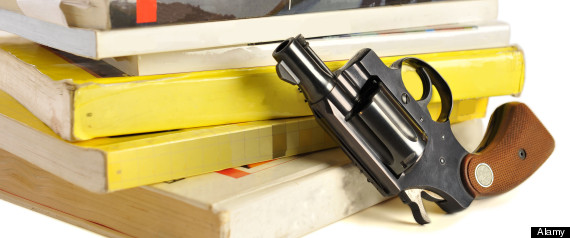 A 38 caliber pistol stands in front of school textbooks, isolated on white, focus on gun barrel